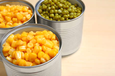 Open tin cans of sweet corn and peas on table, closeup. Space for text