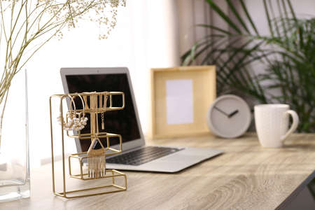 Stylish workplace interior with jewelry holder on wooden table near window. Space for text Stock Photo