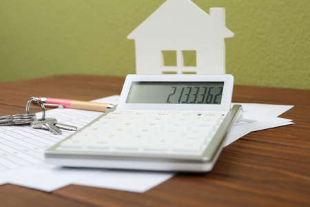 Calculator, house model, keys and documents on wooden table. Real estate agents workplace