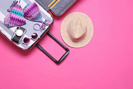 Open suitcase and beach objects on pink background, flat lay. Space for text