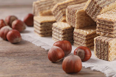 Delicious wafers with hazelnuts on brown wooden background, closeup