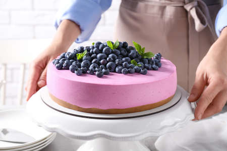 Young woman with tasty blueberry cake at table, closeup