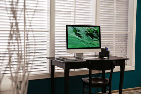 Comfortable workplace near window with white horizontal blinds in room 写真素材