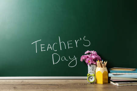Green chalkboard with inscription TEACHER'S DAY and vase of flowers on wooden table