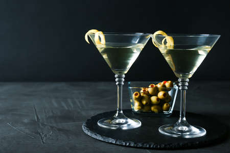 Glasses of Lemon Drop Martini cocktail with zest on grey table against black background. Space for text