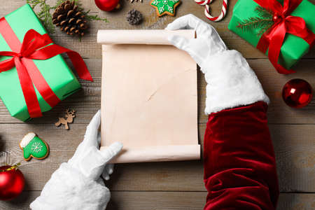 Santa Claus holding empty paper at wooden table, top view. Space for text