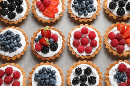 Different berry tarts on table, flat lay. Delicious pastries 스톡 콘텐츠