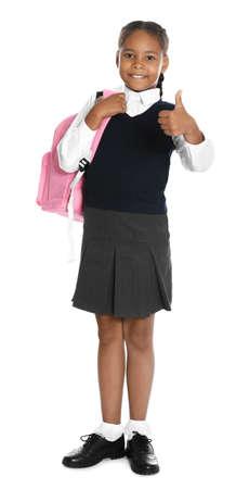 Feliz niña afroamericana en uniforme escolar sobre fondo blanco.