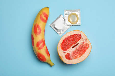 Condoms, cut grapefruit and banana with lipstick kiss marks on light blue background, flat lay. Safe sex