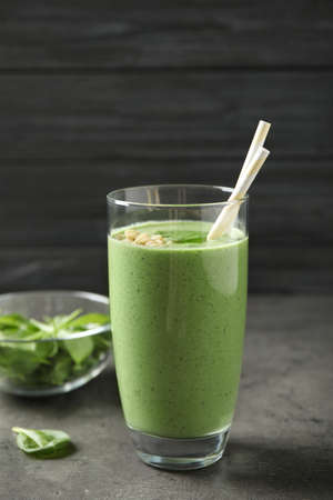 Glass of healthy green smoothie with fresh spinach on grey table