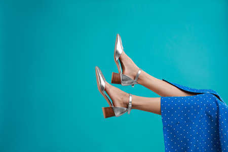 Woman in stylish shoes on light blue background. Space for text Archivio Fotografico - 129795304