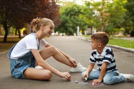 Niñera adolescente y lindo niño dibujo con tizas sobre asfalto
