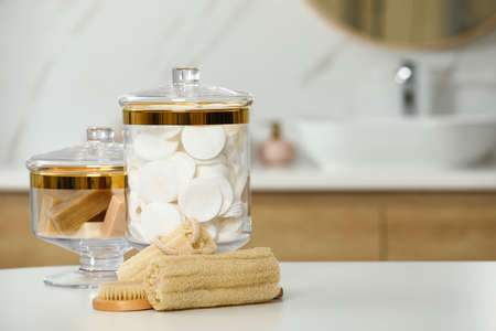 Composition of glass jar with cotton pads on table in bathroom. Space for text 写真素材 - 129795316