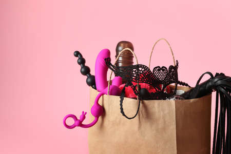 Paper shopping bag with different sex toys on pink background 写真素材