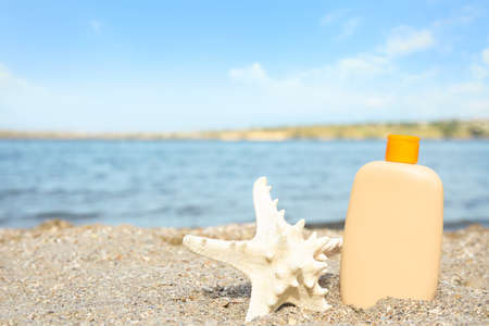 Bottle of sun protection body cream and starfish on beach, space for design