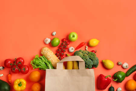 Paper bag with different groceries on coral background, flat lay