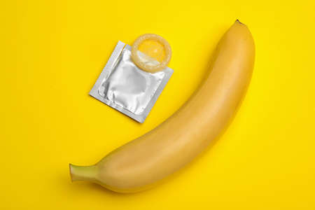 Condom and banana on yellow background, flat lay. Safe sex 写真素材