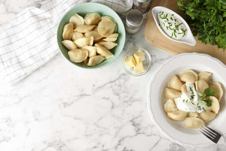 Delicious cooked dumplings with sour cream on white marble table, flat lay. Space for text Stockfoto