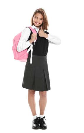 Niña feliz en uniforme escolar sobre fondo blanco.