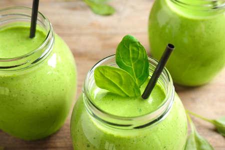 Frascos de batido verde saludable con espinacas frescas en la mesa de madera, vista de cerca