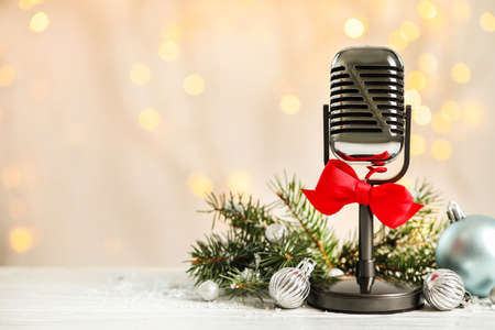 Microphone with red bow and decorations on white table against blurred lights, space for text. Christmas music Archivio Fotografico - 129796147