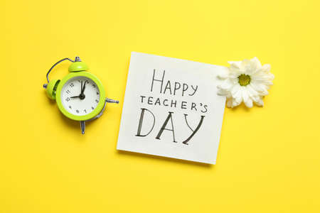 Flat lay composition of card with inscription HAPPY TEACHERS DAY, flower and alarm clock on yellow background Imagens