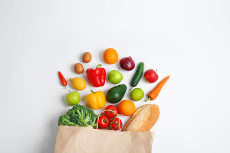 Paper bag with different groceries on white background, top view 写真素材