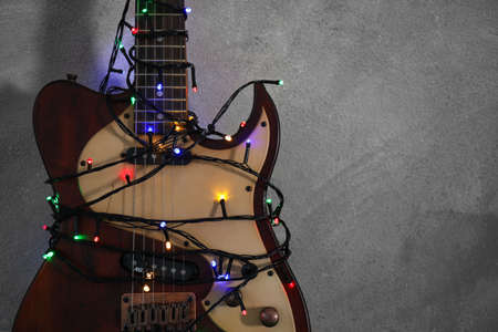 Guitar with colorful lights on grey stone background, space for text. Christmas music