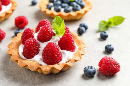 Delicious sweet pastry with berries on grey table Imagens