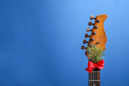 Guitar with red bow and fir branch on blue background, space for text. Christmas music Stock Photo - 129796797