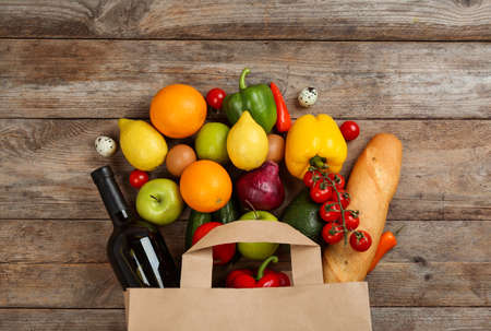 Flat lay composition with overturned paper bag and groceries on wooden table Reklamní fotografie