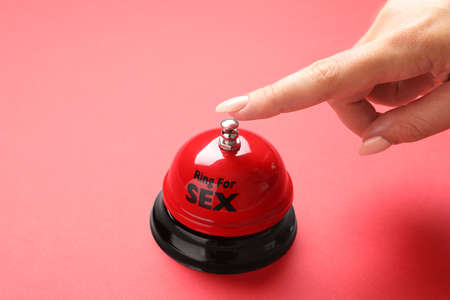 Young woman with sex bell on red background, closeup 写真素材