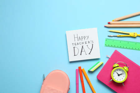 Flat lay composition of card with inscription HAPPY TEACHERS DAY and stationery on light blue background, space for text Imagens