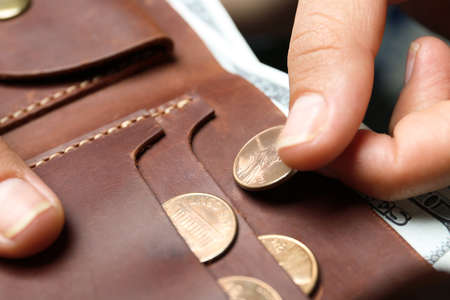 Young woman putting coin into wallet, closeup Stockfoto