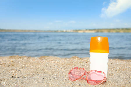 Bottle of sun protection body cream and glasses on beach, space for design