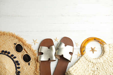 Flat lay composition with beach objects on white wooden background. Space for text
