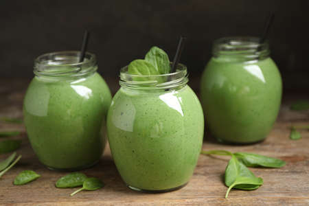 Jars of healthy green smoothie with fresh spinach on wooden table Stock fotó