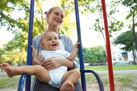 Nounou adolescente avec mignon petit bébé sur la balançoire à l'extérieur Banque d'images