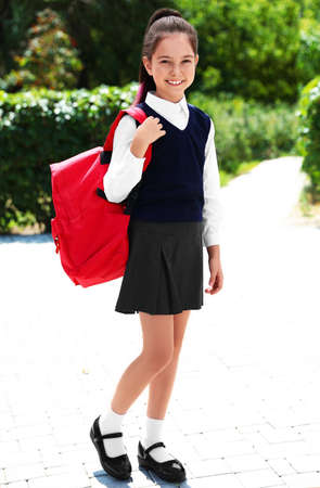 Cute little girl in school uniform with red backpack on street