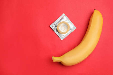 Condom with banana and space for text on red background, flat lay. Safe sex