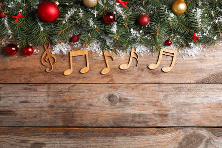 Flat lay composition with Christmas decor and music notes on wooden table, space for text Archivio Fotografico - 129798300