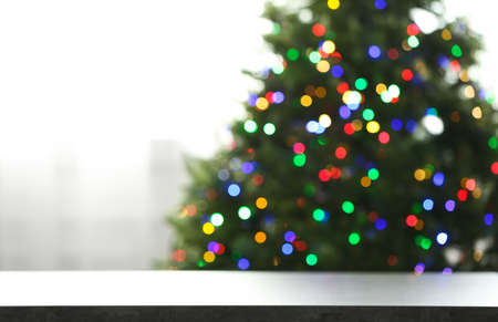 Empty table and blurred fir tree with colorful Christmas lights on background, bokeh effect. Space for design