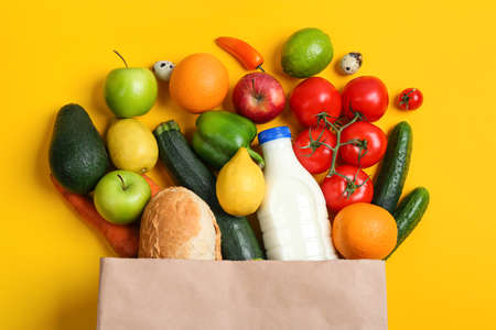Paper bag with different groceries on yellow background, flat lay Reklamní fotografie