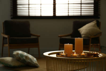 Burning decorative candles on table in room