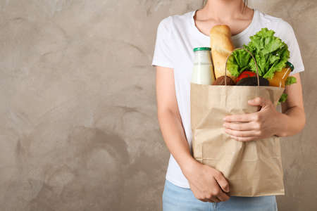 Woman holding shopping paper bag with different groceries against brown background. Space for text Reklamní fotografie