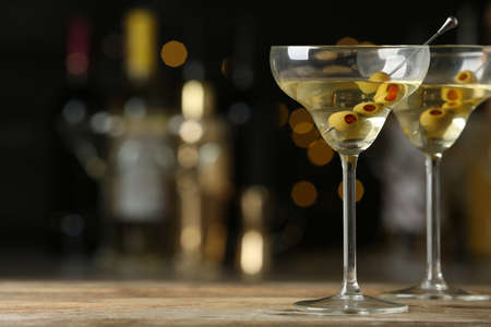 Glasses of Classic Dry Martini with olives on wooden table against blurred background. Space for text