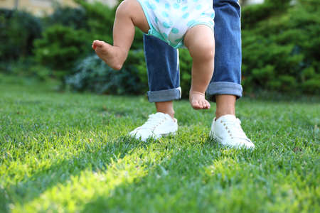 Schattige kleine baby leren lopen met zijn oppas op groen gras buitenshuis, close-up