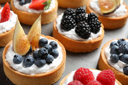Many different berry tarts on table, closeup. Delicious pastries