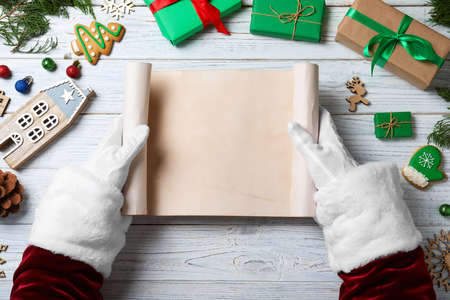 Santa Claus holding empty paper at white wooden table, top view. Space for text