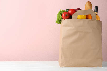 Shopping paper bag with different groceries on table against pink background. Space for text